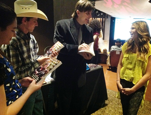 Co-author Randall Franks signs a book sharing Violet's story with youth fiddlers (from left) Ivy Phillips, Jacob Johnson and Cara DiGiaovanni at the Country Music Hall of Fame and Museum in Nashville, Tennessee